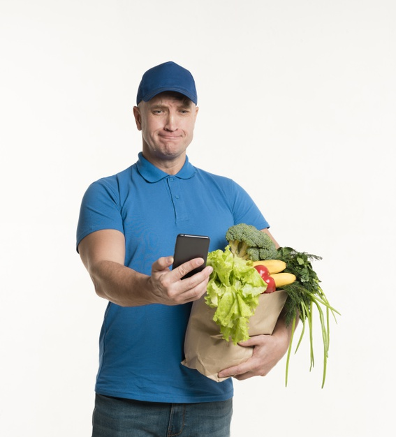 delivery-man-looking-smartphone-while-holding-grocery-bag_23-2148382456